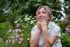 Close up portrait of mature caucasian woman dreaming. In blooming garden Stock Photo
