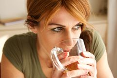 Mature woman drinking a cup of tea. Close up portrait of mature caucasian woman drinking a cup of tea at home and looking away Stock Images