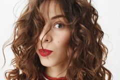 Close-up portrait of mature good-looking woman with curly hairstyle and red lipstick glancing at camera with sensual and. Playful expression, standing over gray Royalty Free Stock Photos