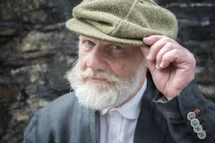 Mature man with white beard and moustache in flat cap. Close up portrait of a mature man with white beard and moustache in flat cap stock image