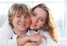Close up portrait of a mature mother and adult daughter being cl Royalty Free Stock Photos