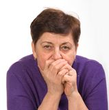 Close-up portrait of mature woman with hands on a mouth Stock Images