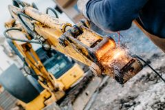 Mechanical engineer working and welding excavator. Close up portrait of mechanical engineer working and welding excavator royalty free stock photography