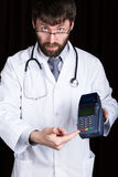 Close-up portrait of a medical doctor, he proposes to pay for treatment in pos-terminal. concept of high cost of the Stock Image