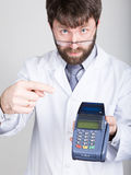 Close-up portrait of a medical doctor, he proposes to pay for treatment in pos-terminal. concept of high cost of the Stock Photos