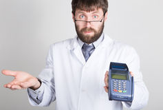 Close-up portrait of a medical doctor, he proposes to pay for treatment in pos-terminal. concept of high cost of the Stock Images