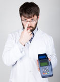 Close-up portrait of a medical doctor, he proposes to pay for treatment in pos-terminal. concept of high cost of the Royalty Free Stock Photos