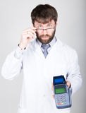 Close-up portrait of a medical doctor, he proposes to pay for treatment in pos-terminal. concept of high cost of the Stock Photography