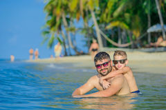Close-up portrait of a men and his son in water: seven years old stock photos