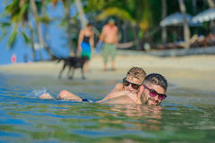 Close-up portrait of a men and his son in water: seven years old royalty free stock image