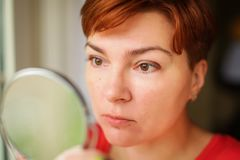 Close up portrait of Middle age woman holding round mirror and carefully looking at her reflection stock photography