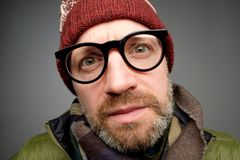 Close up portrait of middle aged europeam man in funny warm hat and glasses noticing hidden camera. stock photo