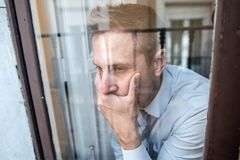 Portrait of middle aged man sad and depressed in mental health concept. Close up portrait of middle aged man sad and depressed looking through the window royalty free stock photos