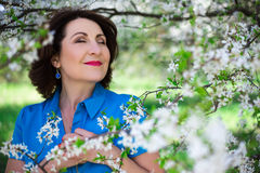 Close up portrait of middle aged woman in cherry garden Stock Image