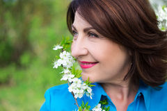 Close up portrait of middle aged woman smelling cherry tree bran Royalty Free Stock Photos