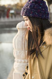 Close-up portrait of a miss traveler. A miss traveler in coat is enjoying the sightseeing of the ancient Houhai lake by stone handrail near famous Gulou Street stock photo