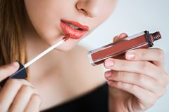 Close up portrait model applying lipstick.. Professional fashion makeup. The girl holds her hand on the lipstick, lip gloss Stock Photography