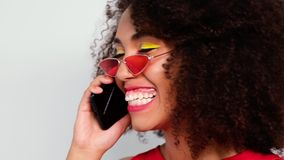 Close-up portrait of model with mobile phone. Close-up portrait of a model with lush curly hair and with a mobile phone in hand. The model is actively talking on stock video