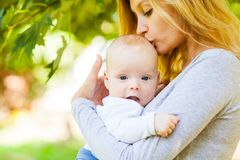 Close up portrait of mother kissing her infant baby royalty free stock image