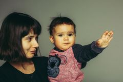 Close up portrait of mother and son. Young mother with short dark hair with her son toddler pointing somewhere Stock Images