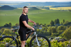 Close-up portrait of the mountain biker looking at beautiful landscape. Royalty Free Stock Image