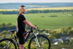 Close-up portrait of the mountain biker looking at beautiful landscape. Stock Photos