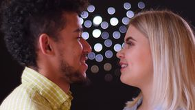 Close-up portrait of multinational couple watching tenderly into eyes on blurred lights background. stock footage