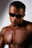 Close-up portrait of a muscular man. Athletic man naked torso wearing sunglasses in the studio Royalty Free Stock Photos