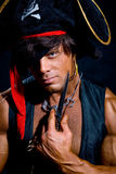 Close-up portrait muscular pirate with a knife on a dark backgro Royalty Free Stock Images