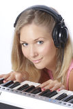 Close-up portrait musician. Young beautiful woman with headphones playing piano. Playing midi-keyboard. DJ-girl playing electronic music. Isolated on white Stock Photos
