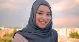 Close-up portrait of muslim student in hijab smiling happily into camera standing at the balcony with great city view. stock video footage