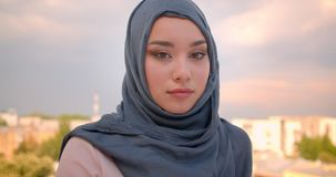 Close-up portrait of muslim student in hijab watching calmly into camera standing at the balcony with great city view. stock footage