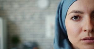 Close-up portrait of Muslim woman in hijab half face on brick wall background. Close-up portrait of attractive Muslim woman in hijab half face on brick wall stock video