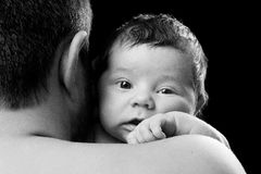 Close-up portrait of a newborn baby in dad's shoulder. Father holding child on a black background.  stock images