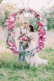 The close-up portrait of the newlyweds holding the bouquet and standing behind the wedding peonies arch in the sunny. Forest Royalty Free Stock Images