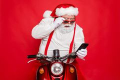 Close-up portrait of nice bearded shocked worried funny funky Santa wearing cap hat sitting on motor bike using cell
