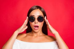 Close-up portrait of nice cool funny amazed attractive charming. Lady wearing white off-the-shoulders top touching glasses opened mouth isolated over red stock images