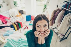 Close-up portrait of nice cute attractive charming funny uncertain worried girl among different clothes difficult choice. Problem in light white interior royalty free stock images