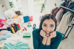 Close-up portrait of nice cute attractive charming pretty scared uncertain worried lady student among different clothes. Difficult choice problem put on in stock photos