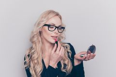 Close-up portrait of nice lovable fascinating gorgeous attractiv. E clever smart intelligent wavy-haired lady holding mirror applying pomade isolated over gray stock photo