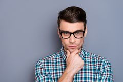 Close-up portrait of nice well-groomed handsome attractive minded guy wearing checked shirt touching chin thinking. Isolated over gray pastel background stock photography