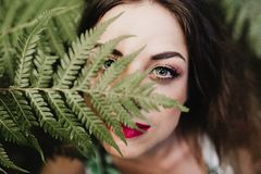 Free Close Up Portrait Of A Young Beautiful Woman Among Green Fern Leaves Looking At The Camera. Beauty Concept Royalty Free Stock Image - 152419116