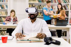 Free Close Up Portrait Of Attractive Focused Young African American Bearded Student Sitting In Library And Reading Book In Vr Stock Photo - 177930290