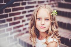 Free Close-up Portrait Of Beautiful 9 -10 Years Old Girl With Blond Curly Hair Sitting On The Stairs. Royalty Free Stock Photos - 179761618