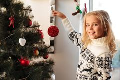 Close-up Portrait Of Pretty Little Girl Holding Red Ball, Looking At Camera At Chrismas Tree Royalty Free Stock Photos