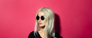 Free Close-up Portrait Of Young Blonde Serious Girl With Glance Away, Wearing Black Round Sunglasses And Shirt, Isolated On Pink Coral. Royalty Free Stock Photography - 173607377