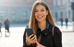 Free Close Up Portrait Of Young Woman Typing On Smart Phone Looking At Camera In City Street In Spring Time Stock Photo - 174173880
