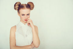 Close-up portrait of offended beautiful girl. with funny hairstyle looking at camera. Stock Photo