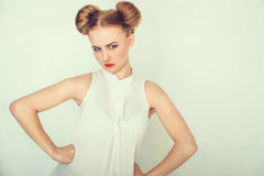 Close-up portrait of offended beautiful girl. with funny hairstyle looking at camera. Royalty Free Stock Photo