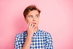 Close up portrait of oh no oops he him his boy biting finger fea. R looking to empty space wearing casual shirts denim plaid outfit isolated on rose background royalty free stock image